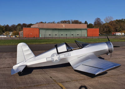 Photo of the ultralight Corsair replica on the runway in front of a colorful hangar building.